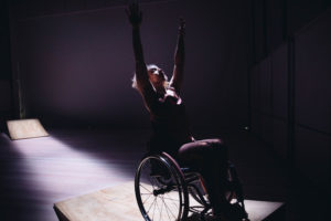 A woman in a wheelchair is backlit in dramatic lighting, and reaches her hands up into the air as she rehearses a dance performance.