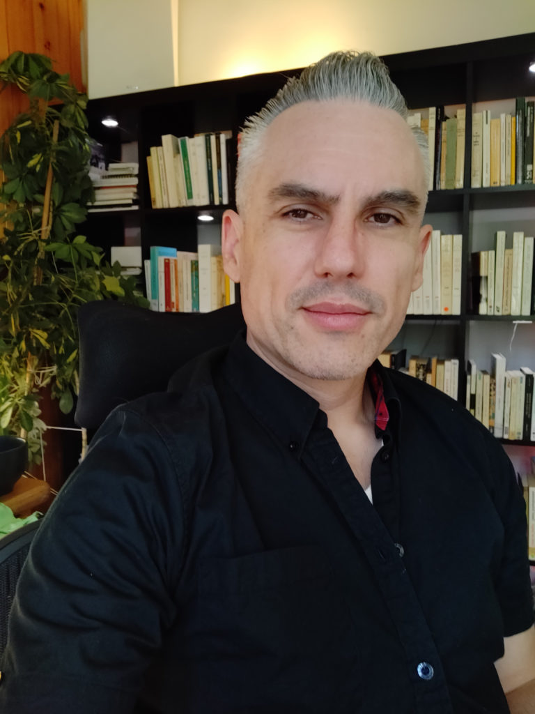 A photo of Yan Grenier, a light-skinned person standing in front of a bookshelf